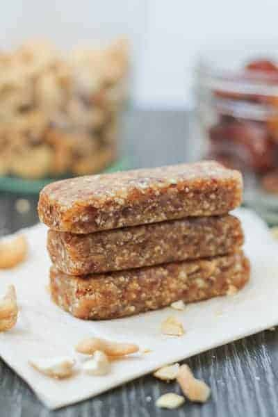 Date Bars on parchment paper with jars of cashews and dates in the background.