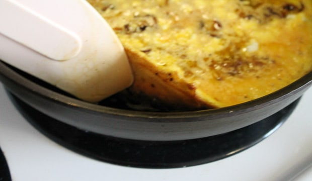 a spatula lifting the side of a frittata in a pan