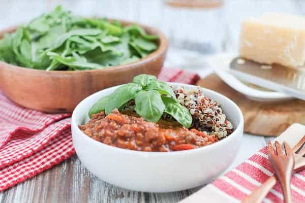 Quinoa & Bolognese Sauce garnished with fresh basil and an arugula salad in a wooden bowl