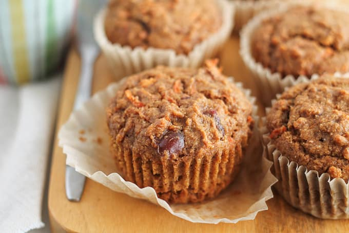 Freshly baked Carrot Date Muffins on a wooden board with a cup of coffee in the background