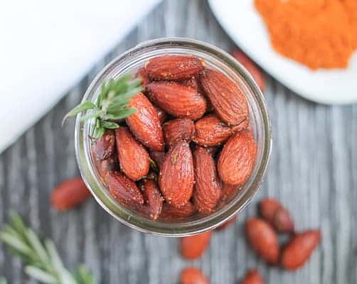 Roasted almonds in a glass jar with a sprig of fresh rosemary tucked in the side and cayenne pepper in a dish in the background