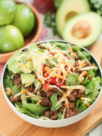 salad topped with spiced beef and shredded cheese with a bowl of fres limes and avocacdo in the background