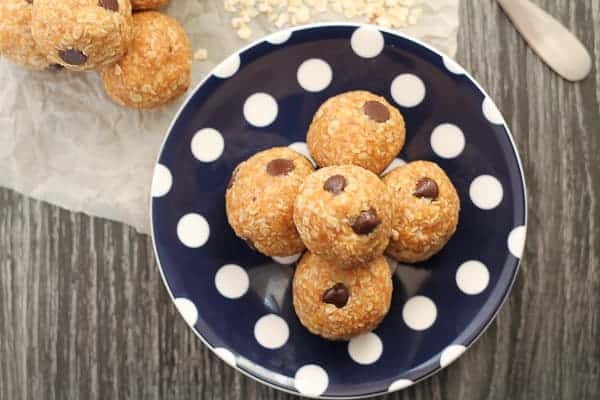 Maple Almond Snack Bites on a polka dot plate with a spoonful of almond butter in the background