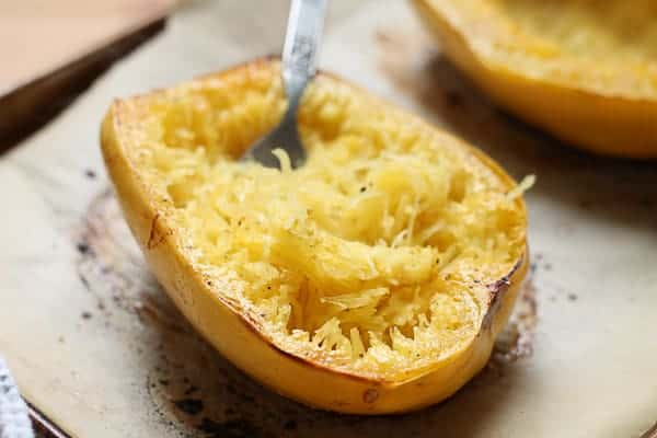 spaghetti squash fresh out of the oven being shredded with a fork