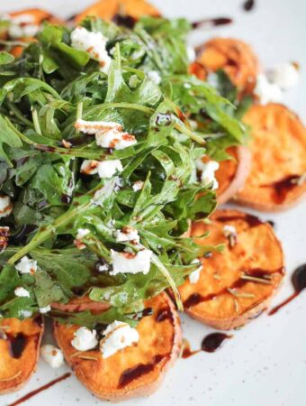 arugula salad topped with crumbled goat cheese served on top of roasted sweet potatoes and drizzled with balsamic glaze