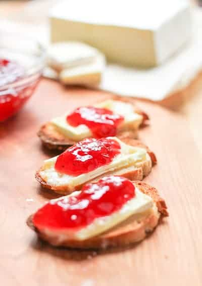Thinly sliced toasted baguette topped with melted brie cheese and strawberry jam on a wooden surface with a jar of jam and sliced brie in the background.
