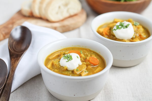 Brown Rice Mulligatawny Soup in a white bowl topped with a dollop of sour cream