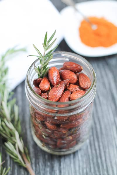 Roasted Almonds in jar with a sprig of rosemary