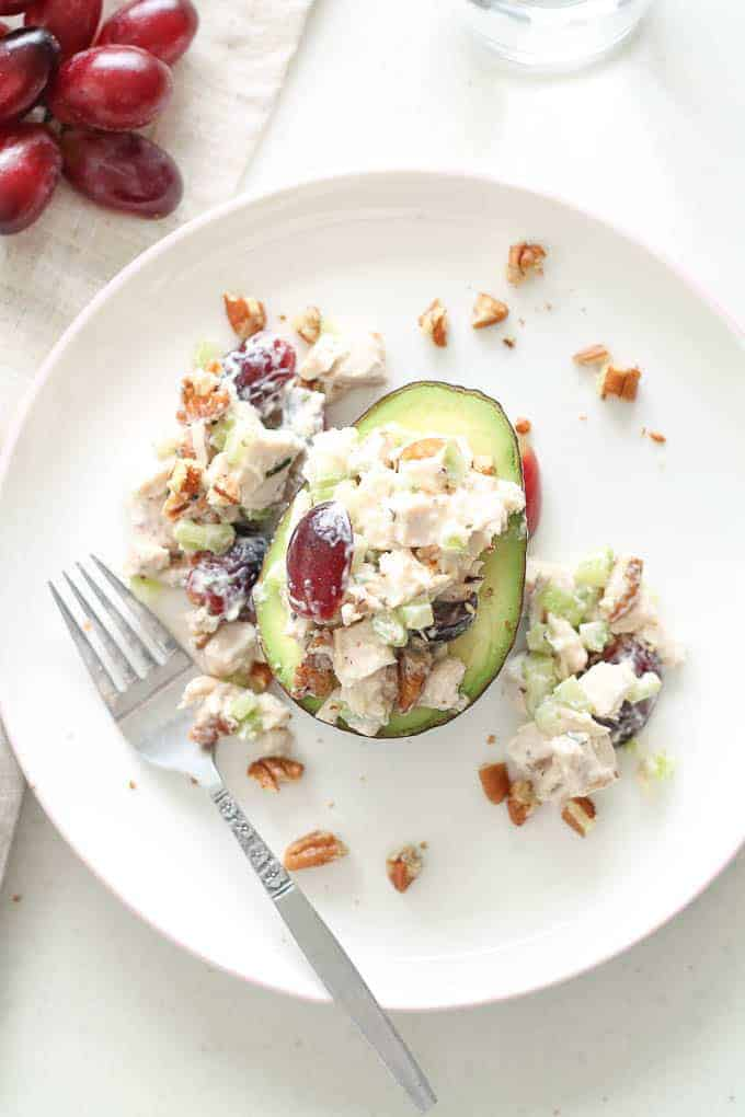 Avocado Chicken salad sits in a avocado shell with toasted pecans and grapes around the plate