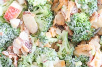creamy broccoli salad tossed in a glass bowl