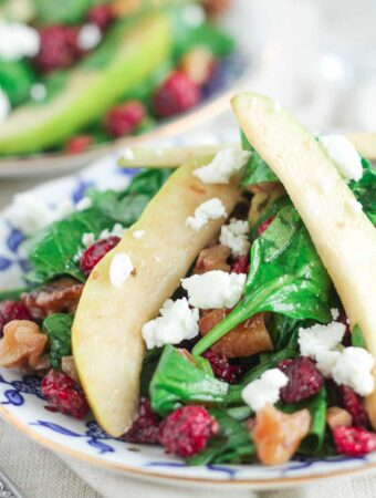 spinach salad with cranberries, pears, walnuts and goat cheese on a plate