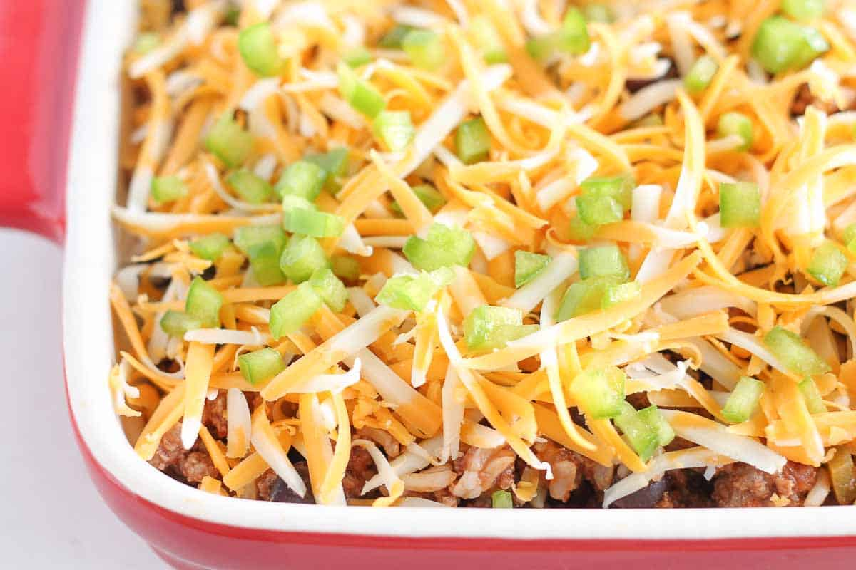 a casserole dish with beef, rice and beans topped with grated cheese and diced peppers
