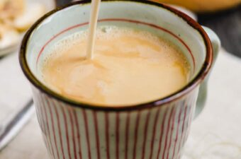 cashew creamer being poured into a mug of coffee.